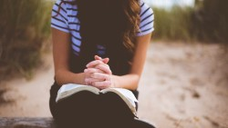 girl-praying-with-bible-religious-stock-photo